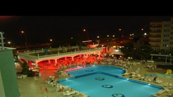 Widok z balkonu na basen, bar i morze noca.
