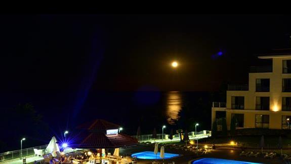 widok z tarasu noca: ksiezyc rozswietlajacy morze