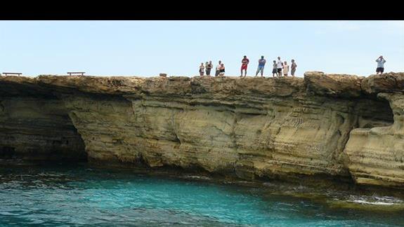 klify i podziwiający wiodki z ich szczytów turyści
