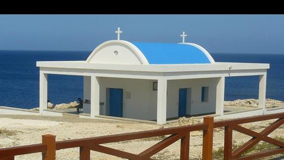 charakterystyczna malownicz akapliczka nad morzem z bielonymi ścianami i niebieskiem dachem