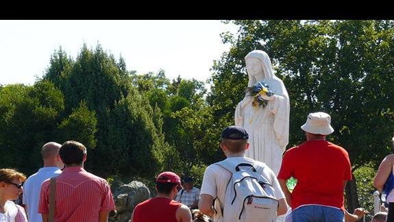 figura Matki Bożej na Wzgórzu Objawień i zgromadzeni wokół niej pielgrzymi