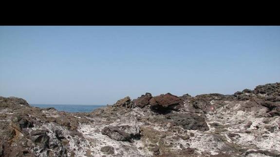Nabrzżne skały wulkaniczne z nalotem soli.
