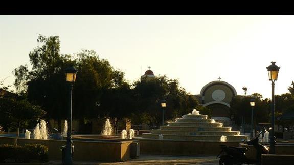 głowny plac miejscowości z charakterystyczną stożkowatą fontanną