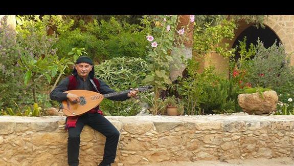 meżczyna w ludowym stroju grający na miejscowym instrumencie - monastyr Agia Napa