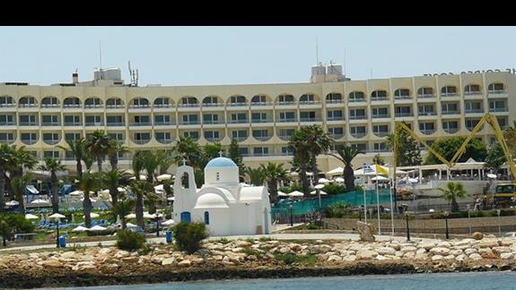 typowa biąło niebieska kapliczka przy ogromnym hotelu
