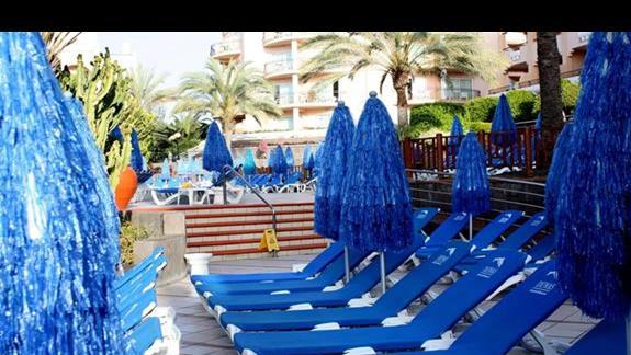 Leżaki i parasole przy basenie