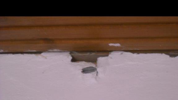 Tuz nad lózkiem dziura w scianie przy suficie i wystajaca rura.