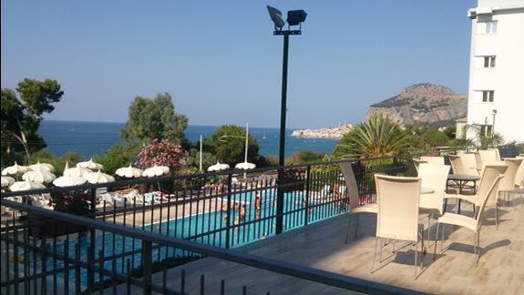 Widok z tarasu od strony basenu, za basenem jest zejście schodami na plażę.