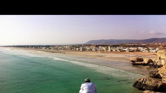 Widok na dluga piaszczysta plaze w Taqah