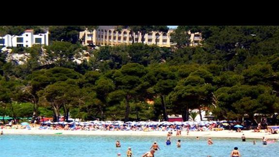 Półokrągły, beżowy hotel Flora Mar widoczny na klifie nad plażą