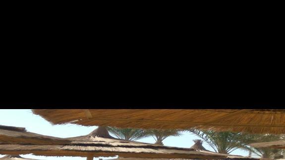 Pracownik rozkłada ręczniki na plaży 7 rano